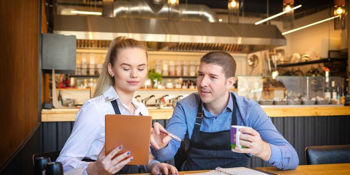 a-cash-register-dealer-showing-the-merchant-how-a-reliable-pos-will-help-his-business-in-saugus-ma