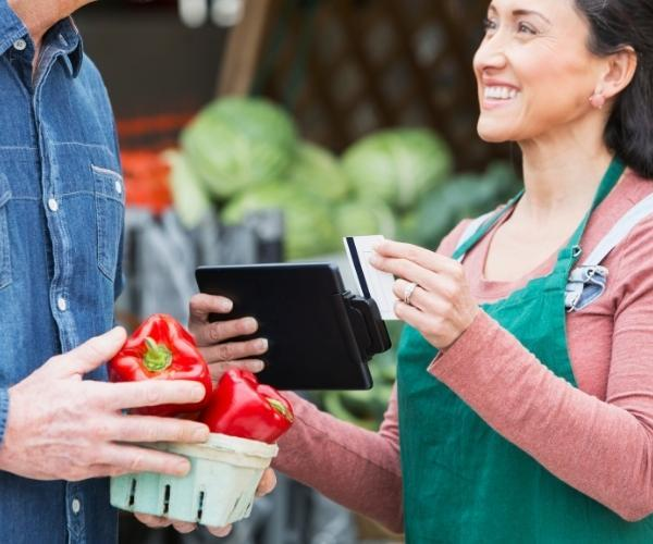 a-man-buying-peppers-with-a-Discover-credit-card