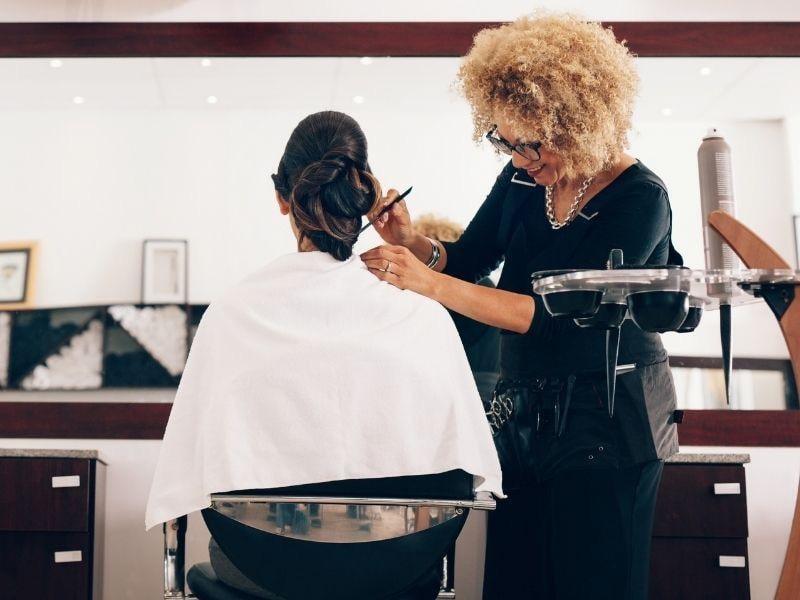 a woman at a hair salon assisting a customer