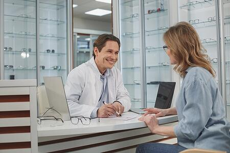 Optometrist collecting a credit card payment from a female patient